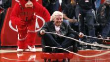 Sir Richard Branson participates in a stunt with Chicago Bulls mascot Bennie The Bull during the second half of an NBA basketball game between the Bulls and the Atlanta Hawks Wednesday, April 15, 2015, in Chicago. The Bulls won 91-85.  - Provided courtesy of AP Photo/Charles Rex Arbogast