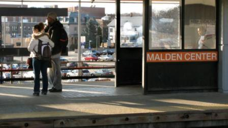 FILE: People wait on the platform of the MBTA station in Malden, Mass.