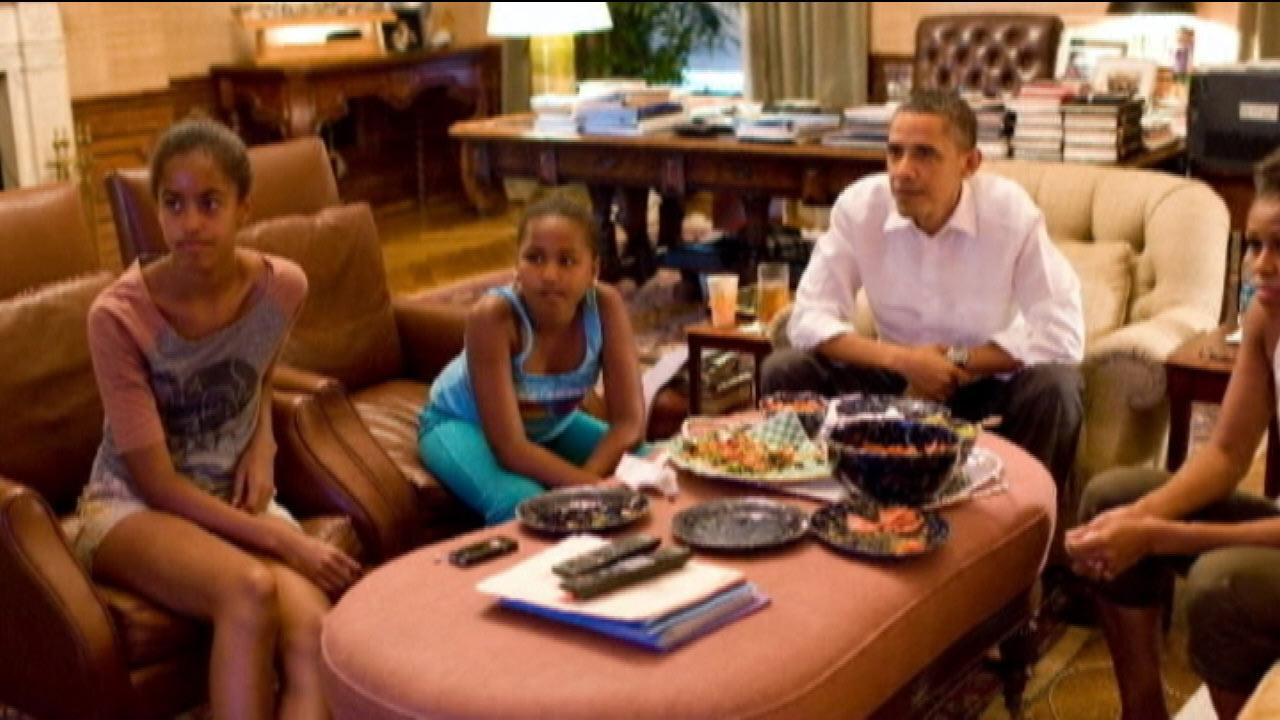 President Obama and his daughters watch football together.
