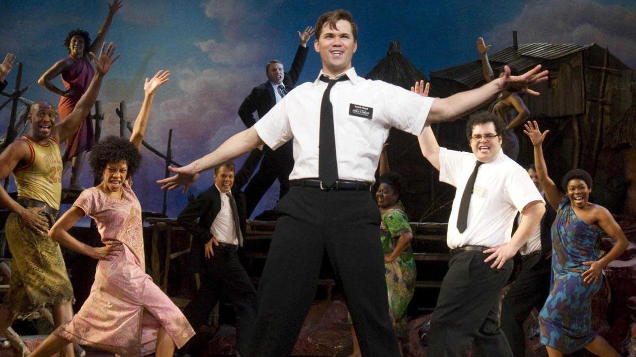 In this theater publicity image released by Boneau/Bryan-Brown, Andrew Rannells, center, performs with an ensemble cast in The Book of Mormon at the Eugene ONeill Theatre in New York.  (AP Photo/Boneau/Bryan-Brown, Joan Marcus)