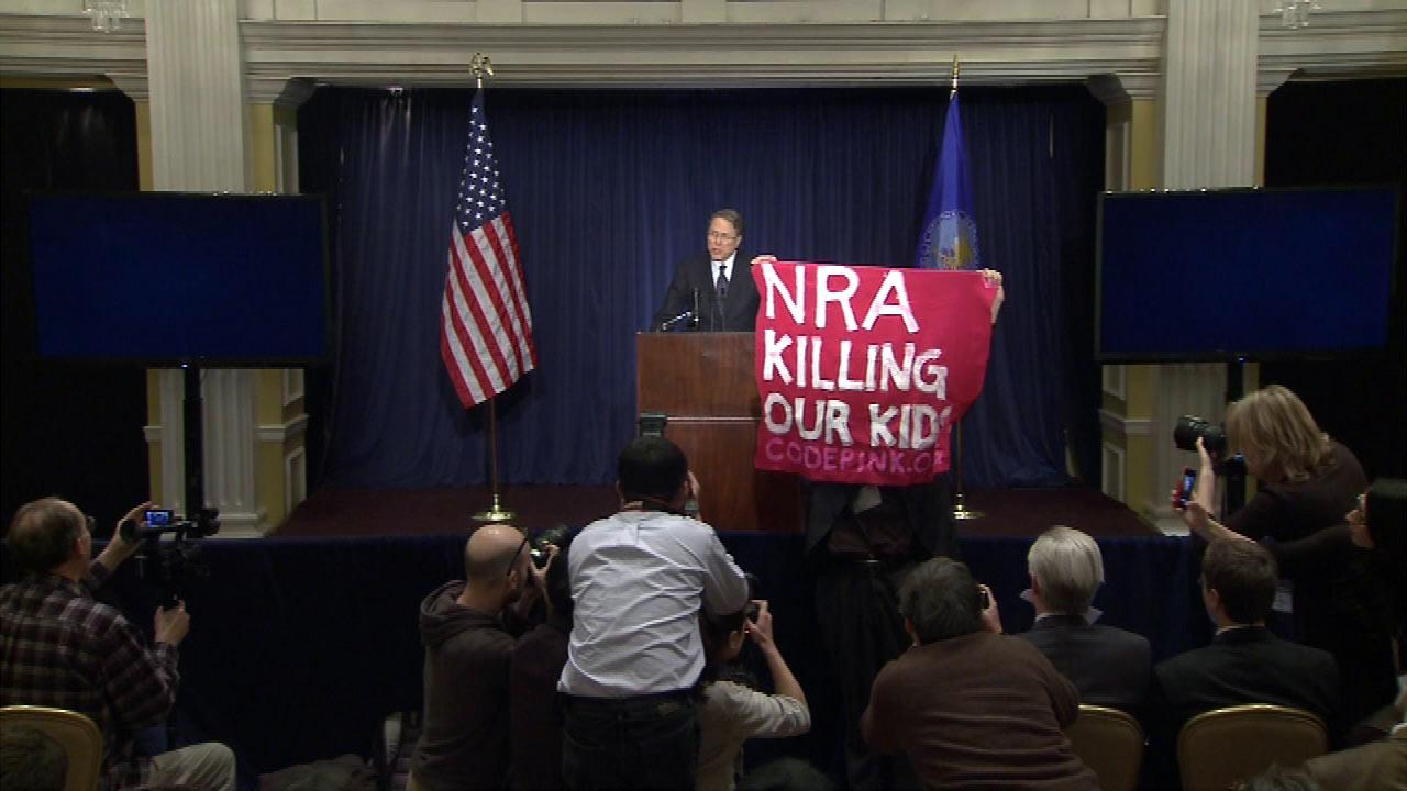The first public National Rifle Association event since the Connecticut school shooting was interrupted twice by people carrying signs protesting the organization, Friday, Dec. 21, 2012.