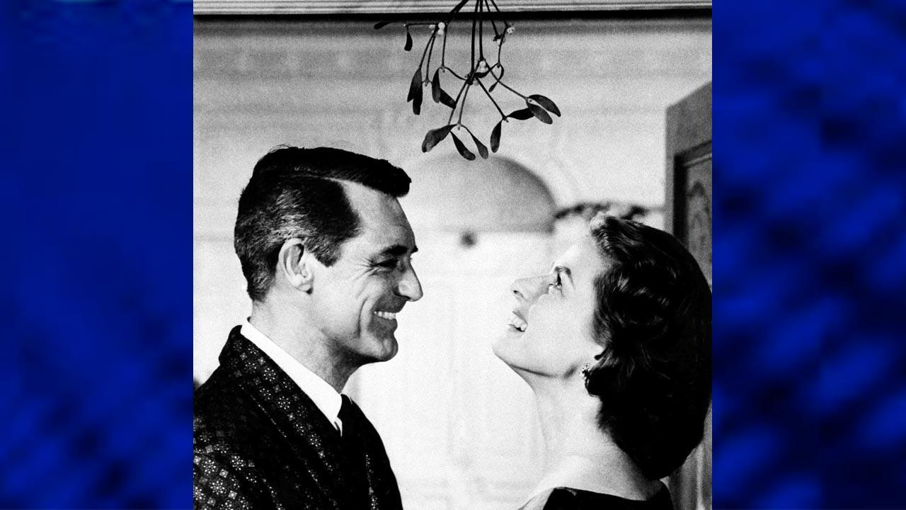 Actor Cary Grant holds actress Ingrid Bergman under the mistletoe, on December 1957 during shooting of a Christmas scene movie in Indiscreet. (AP Photo/Warner Bros)
