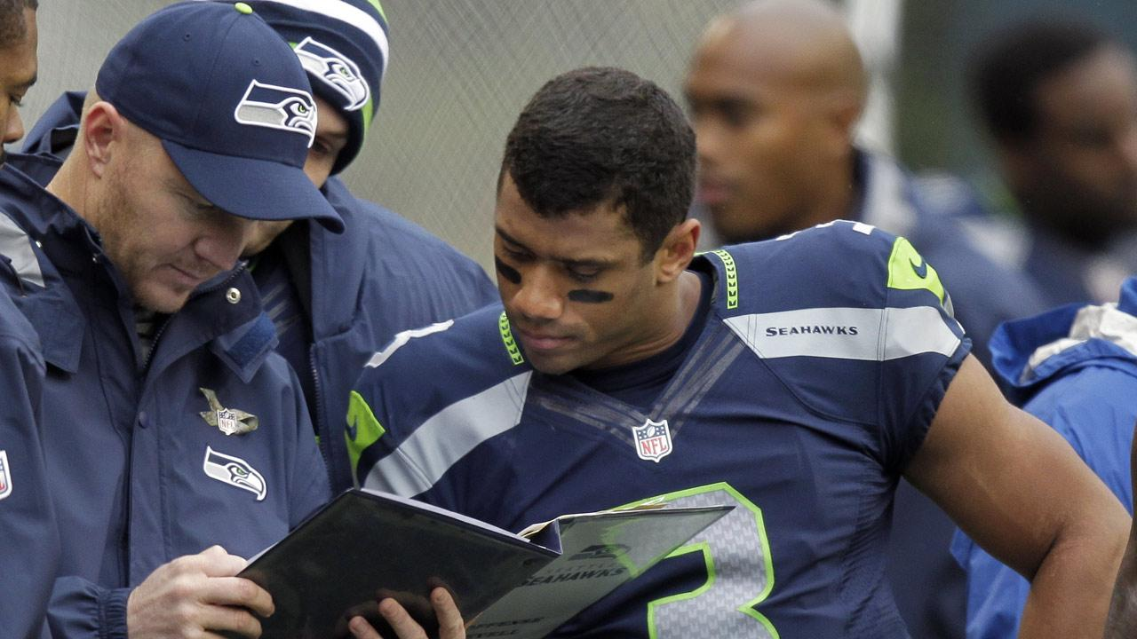 In this Nov. 11, 2012, file photo, Seattle Seahawks offensive coordinator Darrell Bevell looks at a playbook with quarterback Russell Wilson on the sidelines during the first half of an NFL football game against the New York Jets in Seattle. (AP Photo/Stephen Brashear, File)