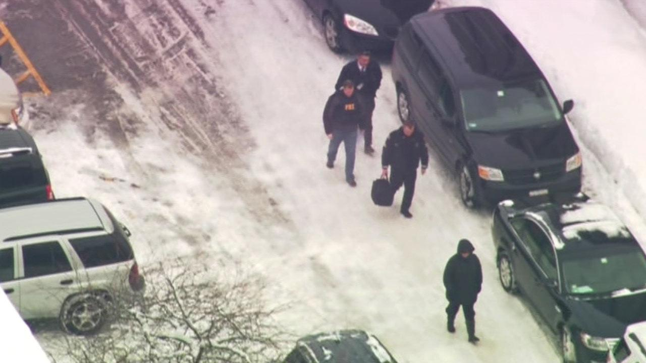 FBI agents deliver a search warrant at the Northern Illinois campus.