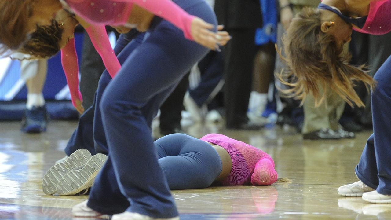 An Atlanta Hawks cheerleader lays on the ground as fellow cheerleaders continue to perform during a dance routine in which hit the floor during the second half of an NBA basketball game against the Dallas Mavericks, Monday, March 18, 2013, in Atlanta. Dallas won 127 to 113. She was taken off the court on a stretcher to a medical facility. (AP Photo/John Amis)