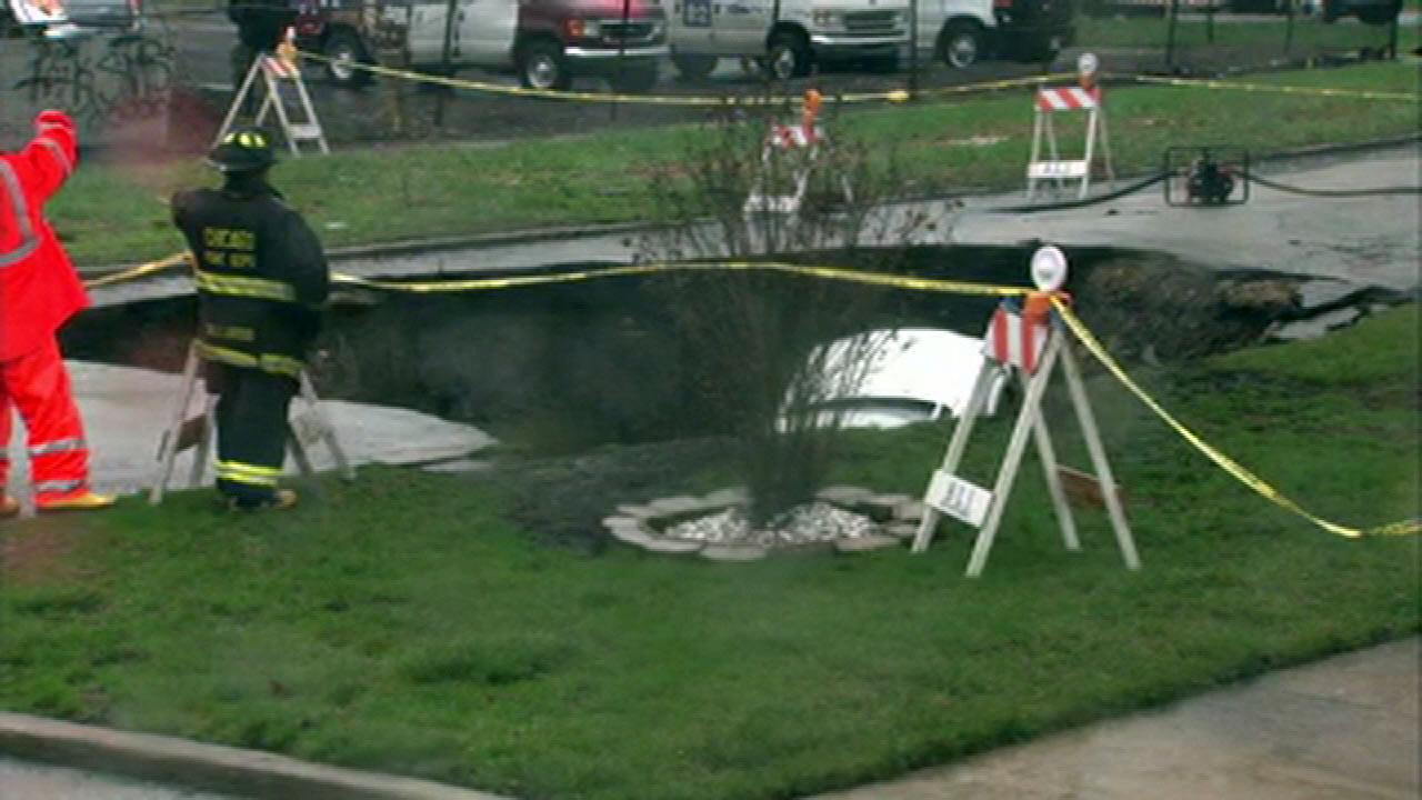Crews worked to remove the vehicles from a sinkhole that swallowed three cars at 96th and Houston in the Jeffery Manor neighborhood. It started to open around 5:15 a.m., Thursday, April 18, 2013.