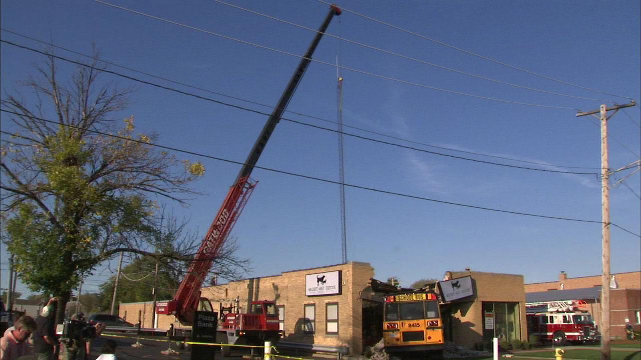 A crane secures the tower on an animal rescue center in Niles after school bus crashed into the building Wednesday afternoon.