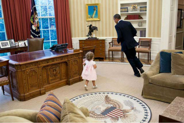 President Barack Obama runs around his desk in the Oval Office with Sarah Froman, daughter of Nancy Goodman and Mike Froman, Deputy National Security Advisor for International Economics, July 9, 2012. &#40;Official White House Photo by Pete Souza&#41; <span class=meta>(Photo&#47;The White House)</span>
