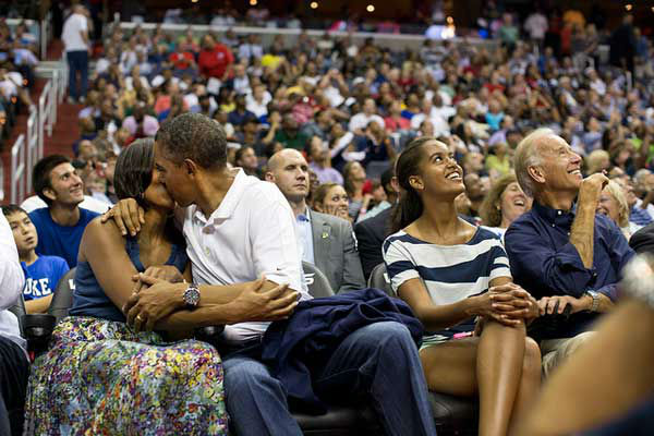 President Barack Obama kisses First Lady Michelle Obama for the &#39;&#39;Kiss Cam&#39;&#39; while attending the U.S. Men&#39;s Olympic basketball team&#39;s game against Brazil at the Verizon Center in Washington, D.C., July 16, 2012. Vice President Joe Biden and Malia Obama look up at the jumbotron. &#40;Official White House Photo by Pete Souza&#41; <span class=meta>(Photo&#47;The White House)</span>