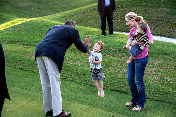 President Barack Obama greets a child on the Kingsmill Resort grounds during a break from debate prep in Williamsburg, Va., Oct. 14, 2012. &#40;Official White House Photo by Pete Souza&#41; <span class=meta>(Photo&#47;The White House)</span>