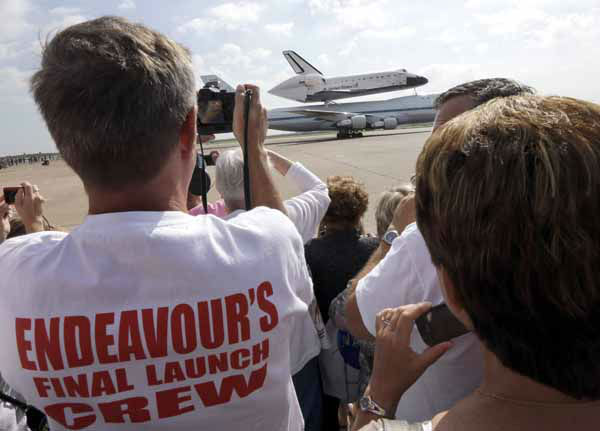 Scott Rush, left, photographs space shuttle Endeavour atop the shuttle aircraft carrier after landing Wednesday, Sept. 19, 2012, at Ellington Field in Houston. Endeavour is making a final trek across the country to the California Science Center in Los Angeles, where it will be permanently displayed. &#40;AP Photo&#47;David J. Phillip <span class=meta>(AP Photo&#47; David J. Phillip)</span>