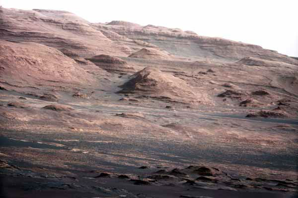 In this image released by NASA on Monday, Aug. 27, 2012, a chapter of the layered geological history of Mars is laid bare in this color image from NASA&#39;s Curiosity rover showing the base of Mount Sharp, the rover&#39;s eventual science destination. The image is a portion of a larger image taken by Curiosity&#39;s 100-millimeter Mast Camera on Aug. 23, 2012. Scientists enhanced the color in one version to show the Martian scene under the lighting conditions we have on Earth, which helps in analyzing the terrain. The pointy mound in the center of the image, looming above the rover-sized rock, is about 1,000 feet &#40;300 meters&#41; across and 300 feet &#40;100 meters&#41; high. &#40;AP Photo&#47;NASA&#47;JPL-Caltech&#47;MSSS&#41; <span class=meta>(AP Photo&#47; DD JN**NY** RJK**NY**)</span>