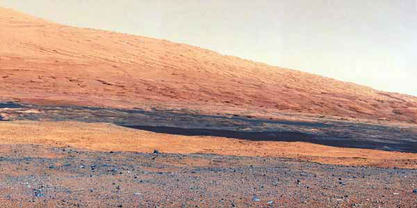 In this image released by NASA on Monday, Aug. 27, 2012, a photo taken by the Mast Camera &#40;MastCam&#41; highlights the geology of Mount Sharp, a mountain inside Gale Crater, where the rover landed. Prior to the rover&#39;s landing on Mars, observations from orbiting satellites indicated that the lower reaches of Mount Sharp, below the line of white dots, are composed of relatively flat-lying strata that bear hydrated minerals. Those orbiter observations did not reveal hydrated minerals in the higher, overlying strata. The MastCam data now reveal a strong discontinuity in the strata above and below the line of white dots, agreeing with the data from orbit. Strata overlying the line of white dots are highly inclined &#40;dipping from left to right&#41; relative to lower, underlying strata. The inclination of these strata above the line of white dots is not obvious from orbit. This provides independent evidence that the absence of hydrated minerals on the upper reaches of Mount Sharp may coincide with a very different formation environment than lower on the slopes. The train of white dots may represent an &#34;unconformity,&#34; or an area where the process of sedimentation stopped. &#40;AP Photo&#47;NASA&#47;JPL-Caltech&#47;MSSS&#41; <span class=meta>(AP Photo&#47; DD JN**NY**)</span>
