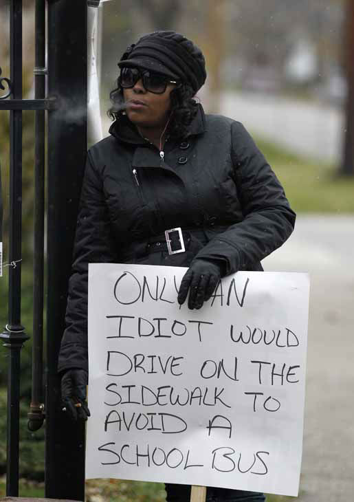 Shena Hardin smokes a cigarette as she holds up a sign to serve a highly public sentence Tuesday, Nov. 13, 2012, in Cleveland, for driving on a sidewalk to avoid a Cleveland school bus that was unloading children. A Cleveland Municipal Court judge ordered 32-year-old Hardin to serve the highly public sentence for one hour Tuesday and Wednesday. &#40;AP Photo&#47;Tony Dejak&#41; <span class=meta>(AP Photo&#47; Tony Dejak)</span>