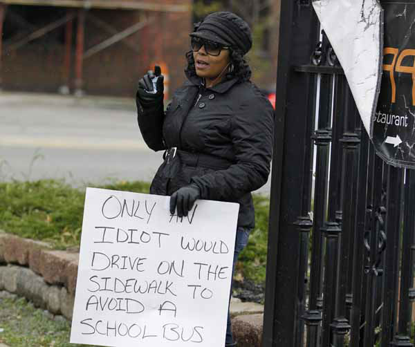 Shena Hardin holds up a sign to serve a highly public sentence Tuesday, Nov. 13, 2012, in Cleveland, for driving on a sidewalk to avoid a Cleveland school bus that was unloading children. A Cleveland Municipal Court judge ordered 32-year-old Hardin to serve the highly public sentence for one hour Tuesday and Wednesday. &#40;AP Photo&#47;Tony Dejak&#41; <span class=meta>(AP Photo&#47; Tony Dejak)</span>