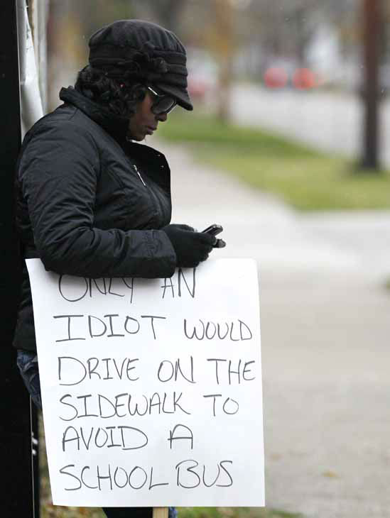 Shena Hardin checks her cell phone as she holds up a sign to serve a highly public sentence Tuesday, Nov. 13, 2012, in Cleveland, for driving on a sidewalk to avoid a Cleveland school bus that was unloading children. A Cleveland Municipal Court judge ordered 32-year-old Hardin to serve the highly public sentence for one hour Tuesday and Wednesday. &#40;AP Photo&#47;Tony Dejak&#41; <span class=meta>(AP Photo&#47; Tony Dejak)</span>