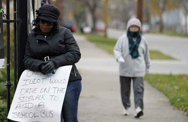 A woman walks by as Shena Hardin, left,  holds up a sign  to serve a highly public sentence Tuesday, Nov. 13, 2012, in Cleveland. Hardin was caught on camera driving on a sidewalk to avoid a Cleveland school bus that was unloading children.  A Cleveland Municipal Court judge ordered 32-year-old Hardin to serve the highly public sentence for one hour Tuesday and Wednesday.&#40;AP Photo&#47;Tony Dejak&#41; <span class=meta>(AP Photo&#47; Tony Dejak)</span>