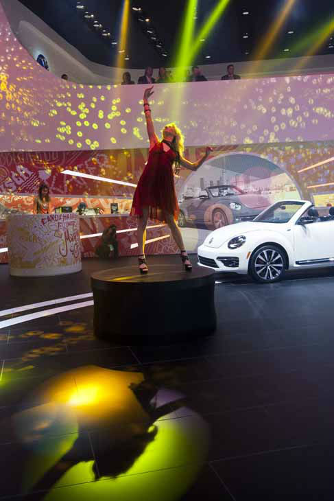 A woman dances to music on a pedestal at the Volkswagen display, at the North American International Auto Show, Monday, Jan. 14, 2013, in Detroit, Mich. &#40;AP Photo&#47;Tony Ding&#41; <span class=meta>(AP Photo&#47; TONY DING)</span>