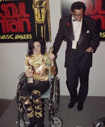 Pop superstar Michael Jackson sits in a wheelchair holding his three Soul Train Music Awards as he is accompanied by Soul Train host Don Cornelius backstage, March 10, 1993, in Los Angeles. Jackson won two trophies for R&#38;B&#47;Soul Album-Male and R&#38;B&#47;Soul Single-Male. he was also presented with a Humanitarian Award.  <span class=meta>(AP Photo&#47;Kevork Djansezian)</span>