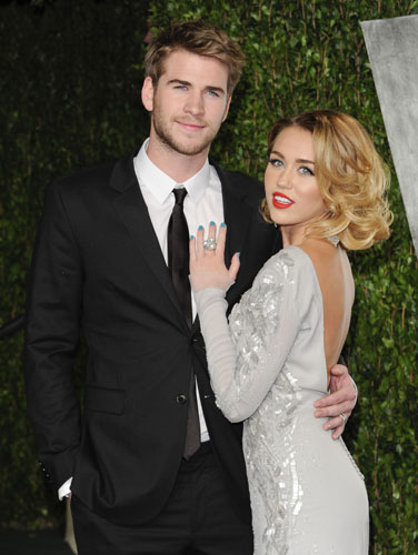 This Feb. 26, 2012 file photo shows Miley Cyrus, right, and Liam Hemsworth at the Vanity Fair Oscar party in West Hollywood, Calif. The couple who met on the set of the movie &#34;The Last Song&#34; in 2009 announced their engagement Wednesday morning. Publicist Jeff Raymond confirms a People Magazine report of the news. Hemsworth, the 22-year-old Australian star of &#34;The Hunger Games,&#34; and Cyrus, the 19-year-old &#34;Hannah Montana&#34; star and singer, were engaged on May 31. Hemsworth proposed with a 3.5-carat diamond ring, People reports.  <span class=meta>(AP Photo&#47;Evan Agostini, file)</span>