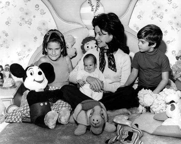 "<div class=""meta image-caption""><div class=""origin-logo origin-image ""><span></span></div><span class=""caption-text"">Actress and former Mouseketeer Annette Funicello holds her infant son, 7-month-old Jason, while watching a revival TV show of the old Mickey Mouse Club series with 9-year-old daughter Gina, and 5-year-old son Jack Jr., at her home in Burbank, Calif., on March 11, 1975. (AP Photo) (AP Photo/ XCB)</span></div>"