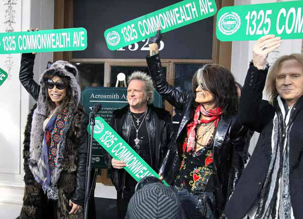 Aerosmith members, from left, Steven Tyler, Joey Kramer, Joe Perry and Tom Hamilton hold up signs Monday, Nov. 5, 2012 at an address in Boston&#39;s Allston neighborhood which was their home in the early 1970&#39;s. Aerosmith later gave a free concert in front of the building. &#40;AP Photo&#47;Elise Amendola&#41; <span class=meta>(AP Photo&#47; Elise Amendola)</span>