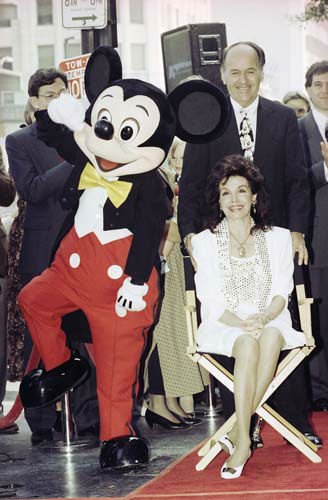 Mickey Mouse dances around as actress and former Mouseketeer Annette Funicello receives a star on the Hollywood Walk of Fame in Los Angeles, Sept. 14, 1993. Behind her is her husband, Glen Holt. Funicello, 50, who has multiple sclerosis, sat in a director&#39;s chair throughout the ceremony. &#40;AP Photo&#47;Kevork Djansezian&#41; <span class=meta>(AP Photo&#47; Kevork Djansezian)</span>