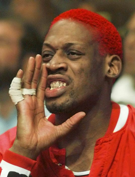 Chicago Bulls' Dennis Rodman, with a new red hair color, shouts from the bench during the first quarter action against the Miami Heat Tuesday, April 2, 1996.  It was Rodman's first game back after serving a six-game suspension for head-butting a referee. (AP Photo/Hans Deryk)