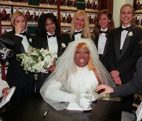 "This Aug. 21, 1996, file photo shows Chicago Bulls forward Dennis Rodman, dressed as a bride, posing for photographers at a New York bookstore while promoting his book, ""Bad As I Wanna Be."" (AP Photo/Mark Lennihan)"
