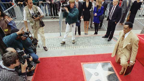 Television producer Don Cornelius kneels in front of photographers near his own star on the Hollywood Walk of Fame during an unveiling ceremony in Los Angeles, Thursday, Feb. 27, 1997.   <span class=meta>(AP Photo&#47;John Hayes)</span>