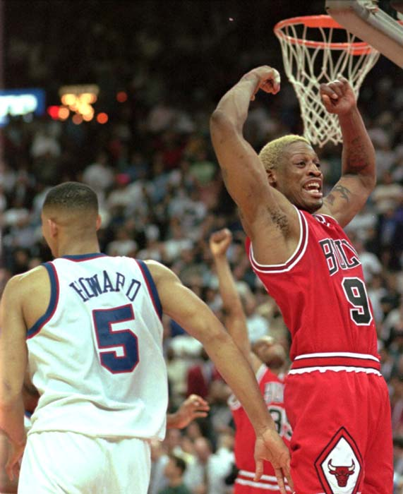 Chicago Bulls Dennis Rodman celebrates the Bulls 96-95 win as dejected Washington Bullets Juwan Howard walks off the court in Landover, Md., Wednesday, April 30, 1997.  The Bulls swept the first round NBA playoff series 3-0. (AP Photo/Roberto Borea)
