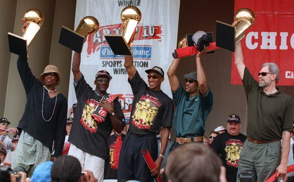 The Chicago Bulls' Dennis Rodman, left, Michael Jordan, Scottie Pippen, Ron Harper and coach Phil Jackson, right, hoist the team's five NBA Championship trophies aloft during a celebration in Chicago's Grant Park on Monday, June 16, 1997.  The Bulls beat the Utah Jazz 4-2 in the best-of-7 NBA Finals.  (AP Photo/Michael Conroy)