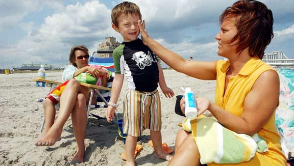 Bernadine Boyce, of Allentown, Pa., applies sunscreen to Bruno Barber, 5, of Atlantic City, as mom, Natalia Barber, watches in Atlantic City, N.J., Friday, June 9, 2006. Experts say the best protection against dangerous cancers like melanoma are sunscreens that contain zinc oxide, titanium dioxide or avobenzone. (AP Photo/Mary Godleski)