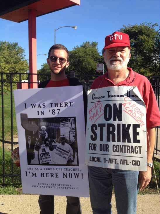 "Viewer-submitted photo via useeit.abc7chicago.com: ""This photo was taken at the Kenwood Academy picket lines this morning. My sign has a photo of me from 1987 on my dad's shoulder when he went on strike as a teacher at Hyde Park Career Academy. He joins me today with the same hat and sign."""