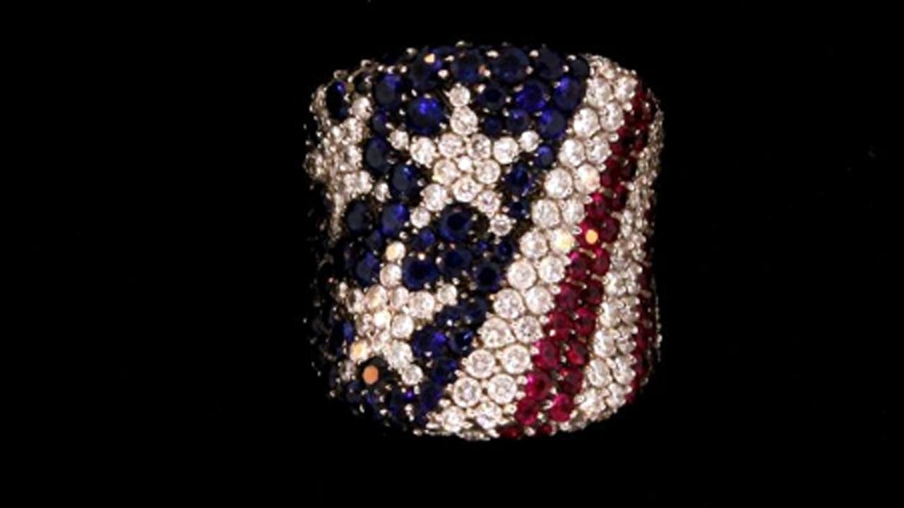 <p> RING: (1) 18kw diamond, ruby and blue sapphire American flag motif ring set with (123) rbc diamonds VS2-SI clarity G-H color, approx. 2.46cttw, (50) rf rubies approx. 1.50 cttw (95) rf blue sapphires, approx. 2.85cttw. Ring is 25mm wide. Size 7. 21.4g.  </p> <p><b><a target_blank hrefhttp://bid.txauction.com/auction.aspx?as26346>Full auction listing here</a></b></p>