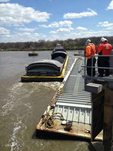Members of the Unified Command watch as one of three additional barges is removed from near the Marseilles Dam in Marseilles, ill., during continued salvage operations, April 25, 2015. Unloading and lightening of three remaining barges will begin this weekend. &#40;Coast Guard photo Lt. Cmdr. David Reinhard&#41; <span class=meta>(Photo&#47;Chief Petty Officer Alan Haraf)</span>