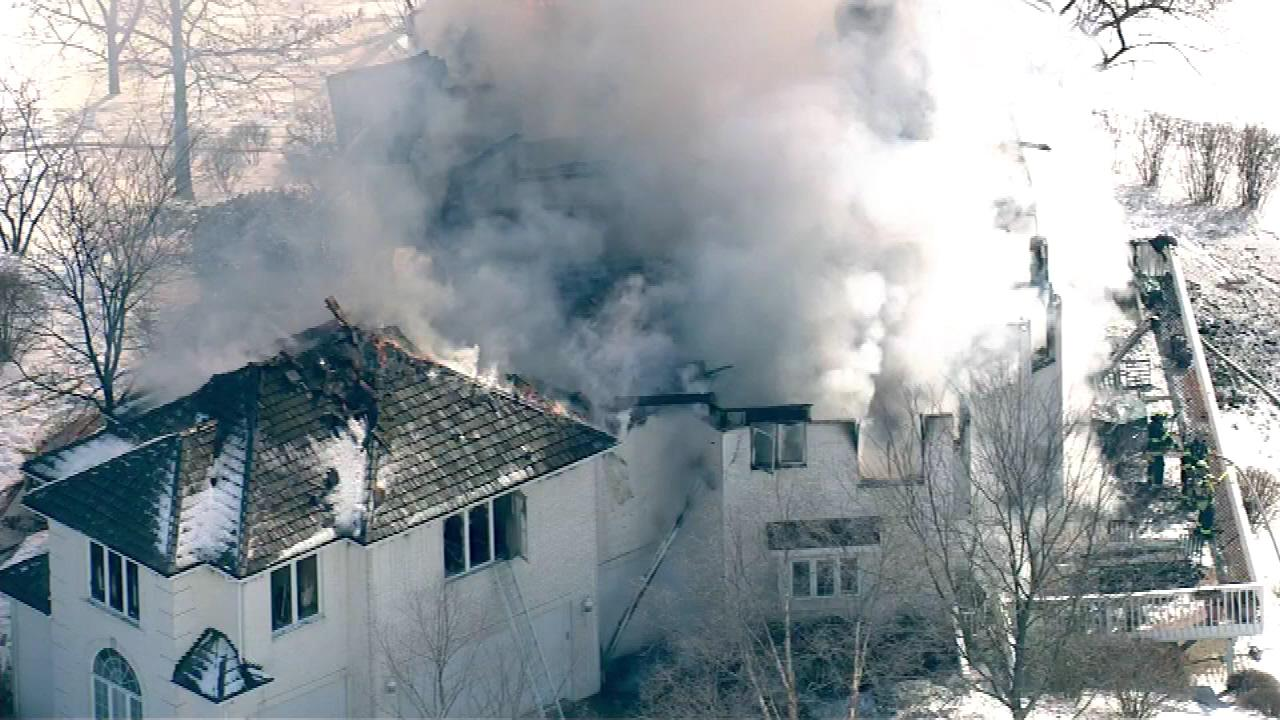 Flames shot through the roof of a mansion-style home in west suburban Burr Ridge Monday.