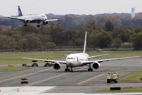 A jet lands near a United Parcel Service jet that is seen isolated on a runway at Philadelphia International Airport in Philadelphia, Friday, Oct. 29, 2010. Law enforcement officials are investigating reports of suspicious packages on cargo planes in Philadelphia and Newark, N.J. (AP Photo/Matt Rourke)