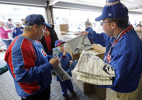 Usher John O&#39;Brien, right, hands out the 1914 replica Chicago Federals&#39; jersey to fans for the 100th anniversary of the first baseball game at Wrigley Field, before a game between the Arizona Diamondbacks and Chicago Cubs,  Wednesday, April 23, 2014, in Chicago. &#40;AP Photo&#47;Charles Rex Arbogast&#41; <span class=meta>(Photo&#47;Charles Rex Arbogast)</span>
