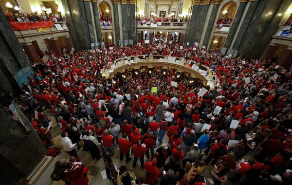 "<div class=""meta image-caption""><div class=""origin-logo origin-image ""><span></span></div><span class=""caption-text"">Protestors of Wisconsin Gov. Scott Walker's bill to eliminate collective bargaining rights for many state workers demonstrate in the rotunda at the State Capitol in Madison, Wis., Thursday, Feb. 17, 2011. (AP Photo/Andy Manis)</span></div>"