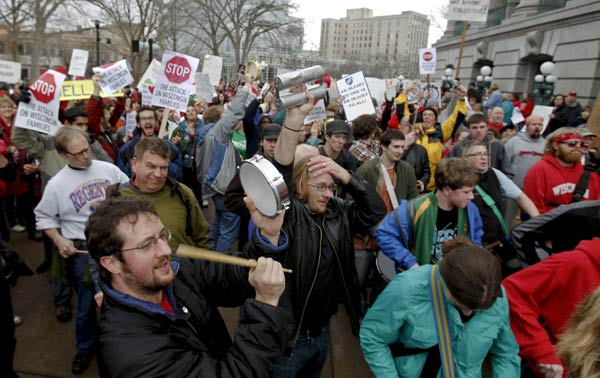 Zach Miller, bottom left, a university staff employee, protests at the State Capitol in Madison, Wis., Thursday, Feb. 17, 2011, the governor's bill to eliminate collective bargaining rights for many state workers. (AP Photo/Andy Manis)