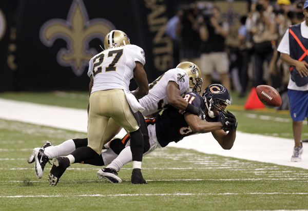 Chicago Bears wide receiver Sam Hurd (81) fumbles out of bounds as he is tackled by New Orleans Saints cornerback Jabari Greer (33) and free safety Malcolm Jenkins (27) during an NFL football game at the Louisiana Superdome in New Orleans, Sunday, Sept. 18, 2011. (AP Photo/Bill Haber)