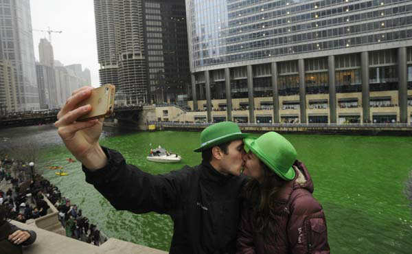 "<div class=""meta image-caption""><div class=""origin-logo origin-image ""><span></span></div><span class=""caption-text"">John Shepard and Gena Damento of Rochester Minn., take a photo of themselves kissing after the Chicago River was dyed green ahead of the St. Patrick's Day parade in Chicago, Saturday, March, 16, 2013.  With the holiday itself falling on a Sunday, many celebrations were scheduled instead for Saturday because of religious observances. (AP Photo/Paul Beaty) (WLS Photo/ PAUL BEATY)</span></div>"