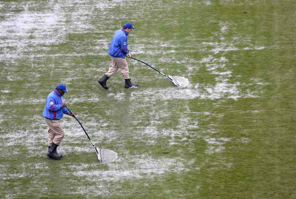 The Wrigley Field grounds crew squeegees water from the infield tarp before an interleague baseball game between the Chicago Cubs and the Texas Rangers Thursday, April 18 2013, in Chicago. Heavy rains forced the postponement of Wednesday&#39;s game and threaten the completion of Thursday&#39;s game. &#40;AP Photo&#47;Charlie Arbogast&#41; <span class=meta>(AP Photo&#47; Charlie Arbogast)</span>