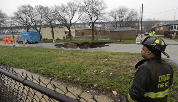 Officials survey a gaping sinkhole that opened up a residential street on Chicago&#39;s South Side after a cast iron water main dating back to 1915 broke during a massive rain storm Thursday, April 18, 2013, in Chicago. The hole spanned the entire width of the road and chewed up grassy areas abutting the sidewalk. Two of the cars that disappeared inside had been parked, but a third was being driven when the road buckled and caved in. Only the hood of one of the vehicles could be seen peeking from the chasm.&#40;AP Photo&#47;M. Spencer Green&#41; <span class=meta>(AP Photo&#47; M. Spencer Green)</span>
