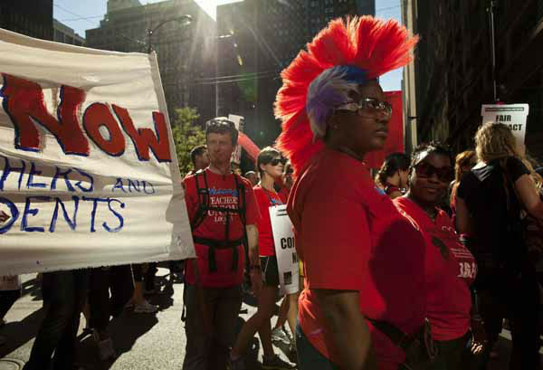 Michelle Harris, a teacher from Kohn School, sports a colourful wig as she marches with thousands of public school teachers for the second consecutive day on Tuesday, Sept. 11, 2012 in downtown Chicago. Teachers walked off the job Monday for the first time in 25 years over issues that include pay raises, classroom conditions, job security and teacher evaluations. &#40;AP Photo&#47;Sitthixay Ditthavong&#41; <span class=meta>(AP Photo&#47; Sitthixay Ditthavong)</span>