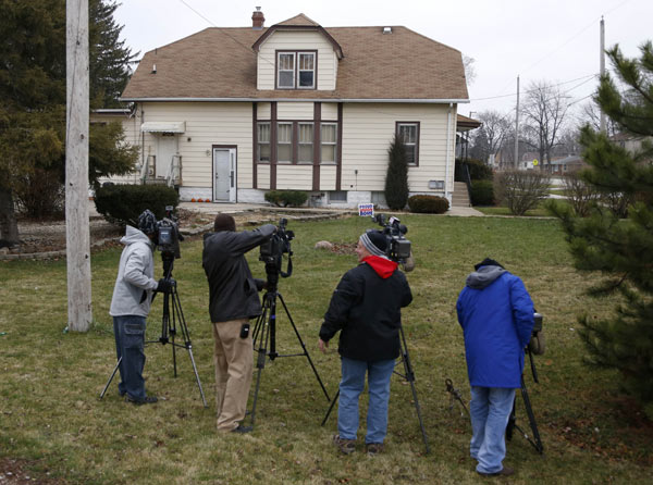 "Television news crews gather outside the home of an unidentified family member of escaped prisoner Kenneth Conley  Tuesday, Dec. 18, 2012, in Tinley Park, Ill. Conley and Joseph ""Jose"" Banks, two convicted bank robbers, escaped from a federal prison window using a knotted rope or bed sheets high above downtown Chicago early Tuesday  according to authorities. Authorities are convinced the two men visited the home before law enforcement officers arrived. (AP Photo/Charles Rex Arbogast)"