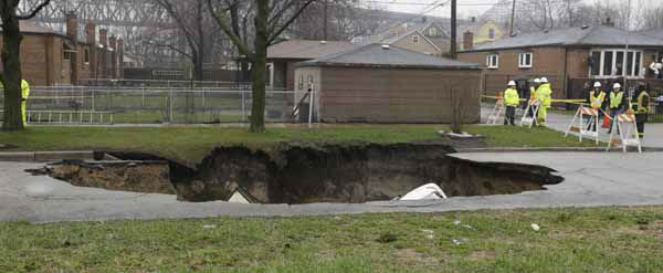 "<div class=""meta image-caption""><div class=""origin-logo origin-image ""><span></span></div><span class=""caption-text"">Officials survey a gaping sinkhole that opened up a residential street on Chicago's South Side after a cast iron water main dating back to 1915 broke during a massive rain storm, Thursday, April 18, 2013, in Chicago. The hole spanned the entire width of the road and chewed up grassy areas abutting the sidewalk. Two of the cars that disappeared inside had been parked, but a third was being driven when the road buckled and caved in. Only the hood of one of the vehicles can be seen peeking from the chasm.(AP Photo/M. Spencer Green) (AP Photo/ M. Spencer Green)</span></div>"