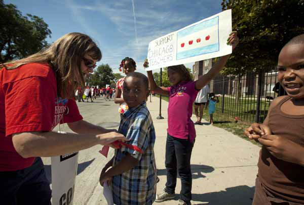 Karen Rieck, a teacher at Faraday Elementary School, greets her students as they show support for public school teachers rallying on Wednesday, Sept. 12, 2012 in West Chicago. Teachers walked off the job Monday for the first time in 25 years over issues that include pay raises, classroom conditions, job security and teacher evaluations. &#40;AP Photo&#47;Sitthixay Ditthavong&#41; <span class=meta>(AP Photo&#47; Sitthixay Ditthavong)</span>
