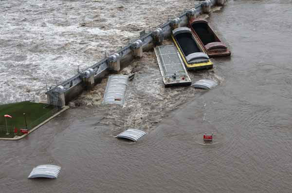 This Thursday, April 18, 2013 photo provided by the U.S. Coast Guard shows the dam in Marseilles, Ill., after seven barges broke free from a tow and came to rest against the dam. Rapid currents from this week&#39;s heavy rainstorms are blamed for the incident. The Coast Guard says the dam sustained minor damage but there were no reports of breaches in the structure or surrounding levees. No one was injured. Authorities evacuated as many as 1,500 residents of the northern city. &#40;AP Photo&#47;Courtesy of the U.S. Coast Guard, Petty Officer 3rd Class John Schleicher&#41; <span class=meta>(AP Photo&#47; John Schleicher)</span>